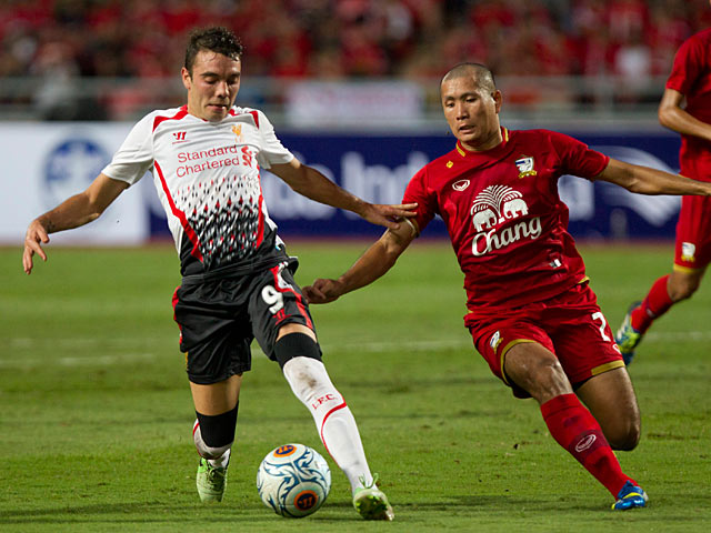 Liverpool's Iago Aspas and Thailand's Pokklao Anun battle for the ball during a friendly match on July 28, 2013