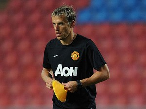 Coach Phil Neville lays out marker cones during a Manchester United training session at Rajamangala Stadium on July 12, 2013