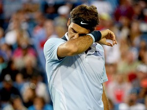 Roger Federer of Switzerland wipes his face between points while playing Rafael Nadal of Spain during the Western & Southern Open on August 16, 2013