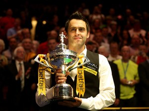 Ronnie O'Sullivan of England poses with the trophy and his son Ronnie after beating Barry Hawkins of England to win the Betfair World Snooker Championship at the Crucible Theatre on May 6, 2013