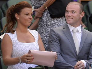 Manchester United footballer Wayne Rooney and his wife Coleen sit in the royal box to watch the men's singles final between Serbia's Novak Djokovic and Britain's Andy Murray on day thirteen of the 2013 Wimbledon Championships tennis tournament at the All