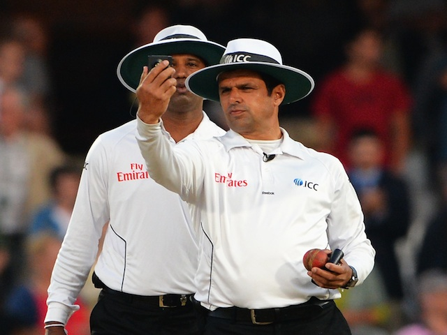 Umpire Aleem Dar takes a light reading on day five of the fifth Ashes test on August 25, 2013