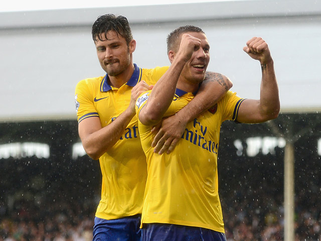 Arsenal's Lukas Podolski celebrates with team mate Olivier Giroud after scoring his team's third goal against Fulham on August 24, 2013