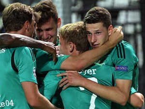 Schalke's Julian Draxler is congratulated by team mates after scoring his team's second goal against PAOK Thessaloniki during their Champions League play-off match on August 27, 2013