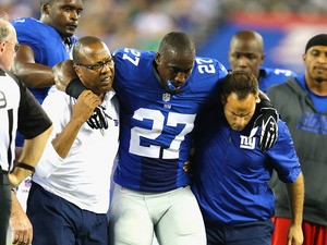 Stevie Brown #27 of the New York Giants is helped off the field after injuring his leg after making an interception against Geno Smith #7 of the New York Jets during their pre season game at MetLife Stadium on August 24, 2013