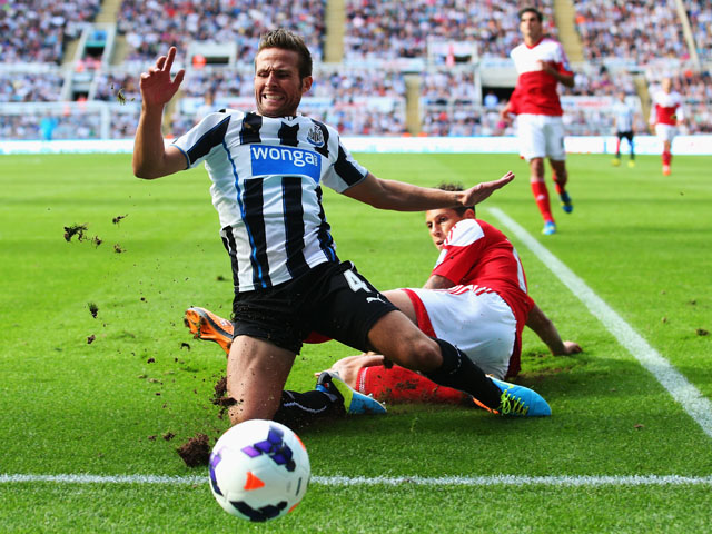 Matthew Briggs of Fulham tackles Yohan Cabaye of Newcastle United from behind during the Barclays Premier League match between Newcastle United and Fulham at St James' Park on August 31, 2013