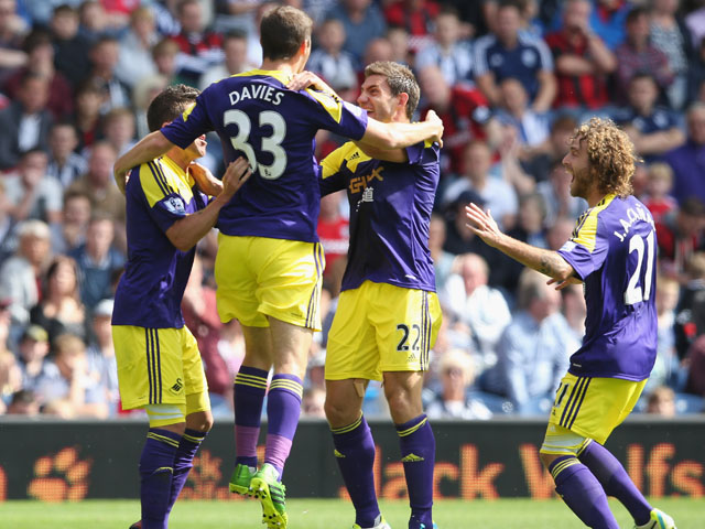 Ben Davies of Swansea City celebrates with team mates after scoring the first goal during the Barclays Premier League match between West Bromwich Albion and Swansea City at The Hawthorns on September 01, 2013