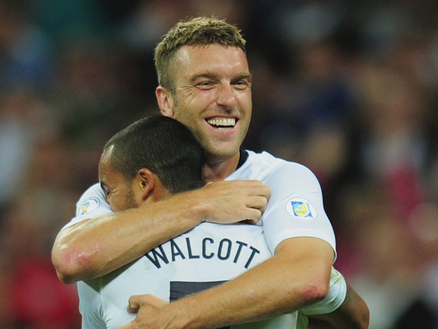 Theo Walcott of England congratulates Rickie Lambert of England on scoring their second goal during the FIFA 2014 World Cup Qualifying Group H match between England and Moldova at Wembley Stadium on September 6, 2013