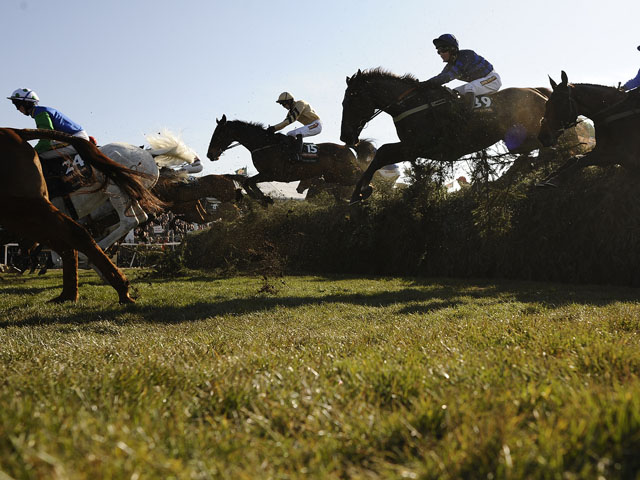 All the runners clear the first fence in The John Smith's Grand National Steeple Chase at Aintree racecourse on April 06, 2013