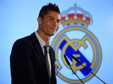 Real Madrid's Cristiano Ronaldo smiles after signing a new contract at the Bernabeu on September 15, 2013