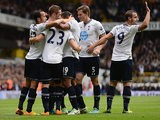 Tottenham's Gylfi Sigurosson is congratulated by team mates after scoring the opening goal against Norwich City on September 14, 2013