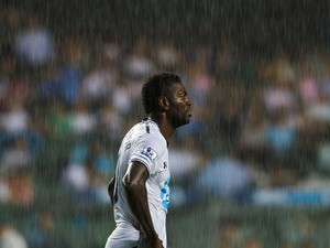 Emmanuel Adebayor of Tottenham Hotspur looks on through heavy rainfall during the Barclays Asia Trophy Semi Final match between Tottenham Hotspur and Sunderland at Hong Kong Stadium on July 24, 2013