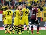 Dortmund's Marcel Schmelzer is congratulated by team mates after scoring the opening goal against Nuremberg during their Bundesliga match on September 21, 2013