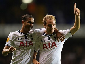 Tottenham's Christian Eriksen celebrates with team mate Kyle Naughton after scoring his team's third goal against Tromso IL during their Europa League group match on September 19, 2013