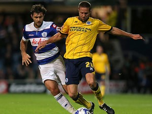 Brighton's Matthew Upson and QPR's Charlie Austin battle for the ball during their Championship match on September 18, 2013