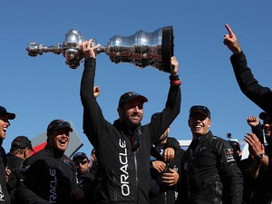 Oracle Team USA tactician Sir Ben Ainslie holds the America's Cup trophy as he celebrates onstage after they beat Emirates Team New Zealand to defend the America's Cup during the final race on September 25, 2013