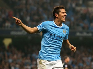 Man City's Stevan Jovetic celebrates after scoring his team's fourth goal against Wigan during their League Cup match on September 24, 2013