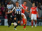 Dan Gosling of Newcasle battles Stewart Drummond of Morecambe during the Capital One Cup Second Round match between Morecambe and Newcastle United at the Globe Arena on August 28, 2013