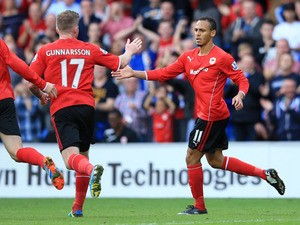 Peter Odemwingie of Cardiff City (R) celebrates with team-mate Aron Gunnarsson after scoring a goal during the Barclays Premier League match between Cardiff City and Newcastle United at Cardiff City Stadium on October 5, 2013