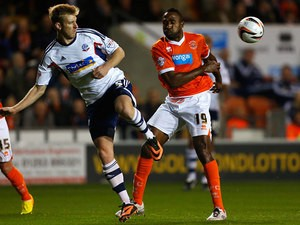 Blackpool's Ricardo Fuller and Bolton's Tim Ream battle for the ball during their Championship match on October 1, 2013