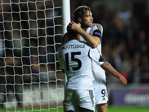 Swansea's Wayne Routledge is congratulated by teammate Michu after scoring the opening goal against St Gallen during their Europa League group match on October 3, 2013