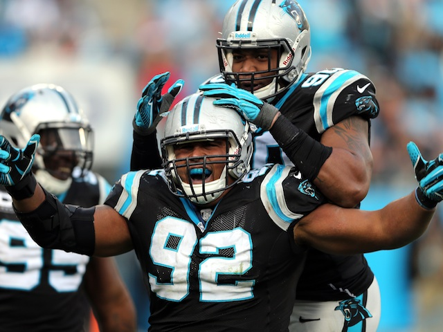 Dwan Edwards of the Carolina Panthers celebrates after a sack with teammate Frank Alexander during their game against the Oakland Raiders on December 23, 2012