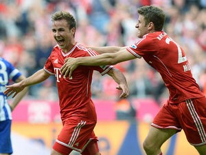 Bayern's Mario Goetze celebrates with team mate Thomas Mueller after scoring his team's third goal against Hertha Berlin on October 26, 2013