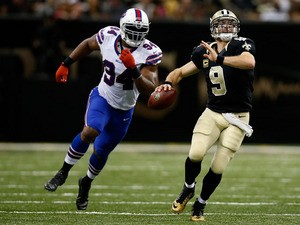 Drew Brees #9 of the New Orleans Saints throws a pass around Mario Williams #94 of the Buffalo Bills at Mercedes-Benz Superdome on October 27, 2013