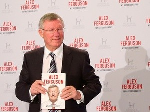 Former Manchester United manager Sir Alex Ferguson poses with his autobiography on October 22, 2013