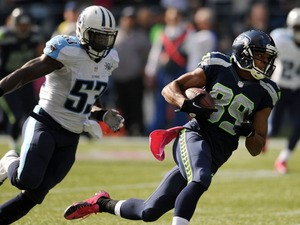 Wide receiver Doug Baldwin #89 of the Seattle Seahawks runs away from middle linebacker Moise Fokou #53 of the Tennessee Titans during the second quarter of the game at CenturyLink Field on October 13, 2013