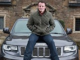 Austin Healey poses on a Jeep after becoming an ambassador for the car company
