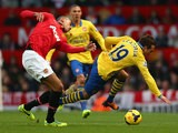 Man United's Chris Smalling and Arsenal's Santi Cazorla battle for the ball on November 10, 2013