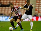 Phil Bardsley of Sunderland vies with Stephen Davis of Southampton during the Capital One Cup fourth Round match between Sunderland and Southampton at Stadium of Light on November 06, 2013