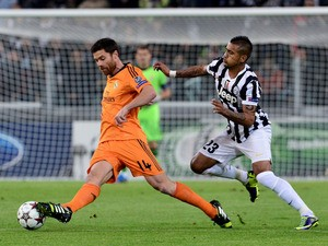 Real Madrid midfielder Xabi Alonso controls the ball in front of Juventus' Chilean midfielder Arturo Vidal on November 5, 2013
