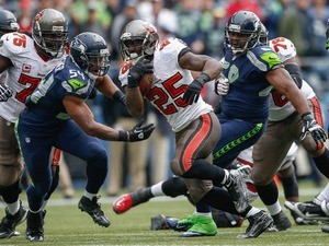 Running back Mike James #25 of the Tampa Bay Buccaneers rushes against middle linebacker Bobby Wagner #54 of the Seattle Seahawks at CenturyLink Field on November 3, 2013