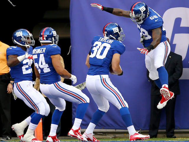 Cooper Taylor of the New York Giants celebrates his touchdown with Allen Bradford after he scored with a blocked punt in the first quarter against the Oakland Raiders on November 10, 2013