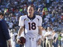 Peyton Manning #18 of the Denver Broncos walks with the football on the sideline during the football game against the San Diego Chargers at Qualcomm Stadium November 10, 2013