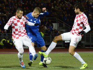 Iceland's midfielder Johann Berg Gudmundsson vies for the ball with Croatia's defender Danijel Pranjic and Croatia's defender Vedran Corluka during the first-leg FIFA World Cup 2014 play-off football match Iceland vs Croatia in Reykjavik, Iceland on Novem