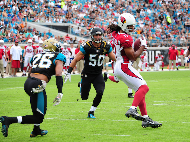 Larry Fitzgerald of the Arizona Cardinals makes a catch for a touchdown against Josh Evans and Russell Allen of the Jacksonville Jaguars on November 17, 2013