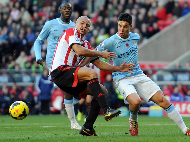 Wes Brown battles for possession with Samir Nasri on November 10, 2013.