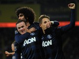 Man United's Wayne Rooney is congratulated by teammates after scoring the opening goal against Cardiff on November 24, 2013