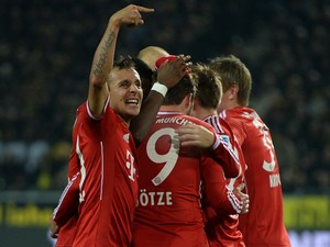 Bayern Munich's players celebrate after scoring the first goal during the German first division Bundesliga football match between Borussia Dortmund on November 23, 2013