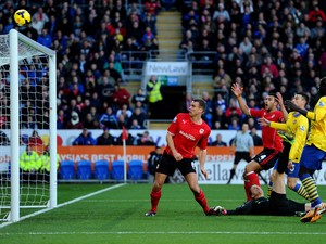 Ben Turner of Cardiff City watches as the ball goes over the crossbar after a challenge with Wojciech Szczesny of Arsenal (grounded) during the Barclays Premier League match between Cardiff City and Arsenal at Cardiff City Stadium on November 30, 2013