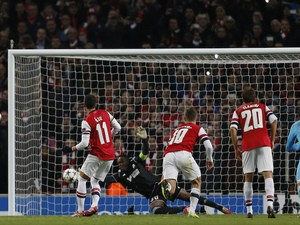 Marseille's French goalkeeper Steve Mandanda saves a penalty taken by Arsenal's German midfielder Mesut Ozil during the UEFA Champions League group F football match on November 26, 2013