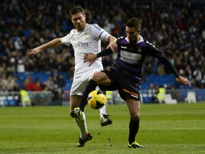 Real Madrid's midfielder Xabi Alonso vies with Valladolid's Italian midfielder Fausto Rossi during the Spanish league football match on November 30, 2013
