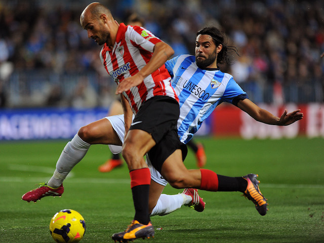 Athletic Bilbao's midfielder Mikel Rico vies with Malaga's defender Sergio Sanchez during the Spanish league football match Malaga CF vs Athletic Club Bilbao at the Rosaleda stadium in Malaga on November 25, 2013