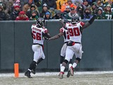 Sean Weatherspoon #56 of the Atlanta Falcons crosses the goalline with teammates including Stansly Maponga #90 after intercepting a pass for a touchdown against the Green Bay Packers at Lambeau Field on December 8, 2013