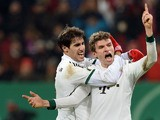 Bayern Munich's Thomas Muller celebrates with teammate Javi Martinez after scoring his team's second goal against Augsburg during their 3rd round German Cup match on December 4, 2013
