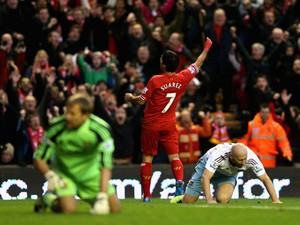 Luis Suarez of Liverpool celebrates after Guy Demel of West Ham United scored an own goal during the Barclays Premier League match between Liverpool and West Ham United at Anfield on December 7, 2013