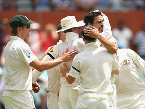 Australia's Mitchell Johnson is congratulated by teammates after taking the wicket of England's Stuart Broad during day three of the second Ashes test on December 7, 2013